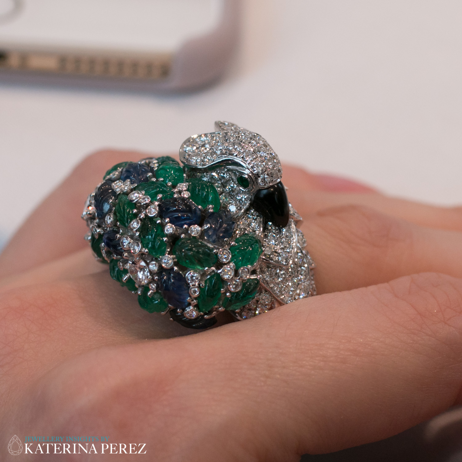 An Onyx, Emerald, Sapphire and Diamond 'Parrot' Ring, by Cartier, circa 1995. Eyes set with circular-cut emeralds, diamonds approximately 3.50 carats