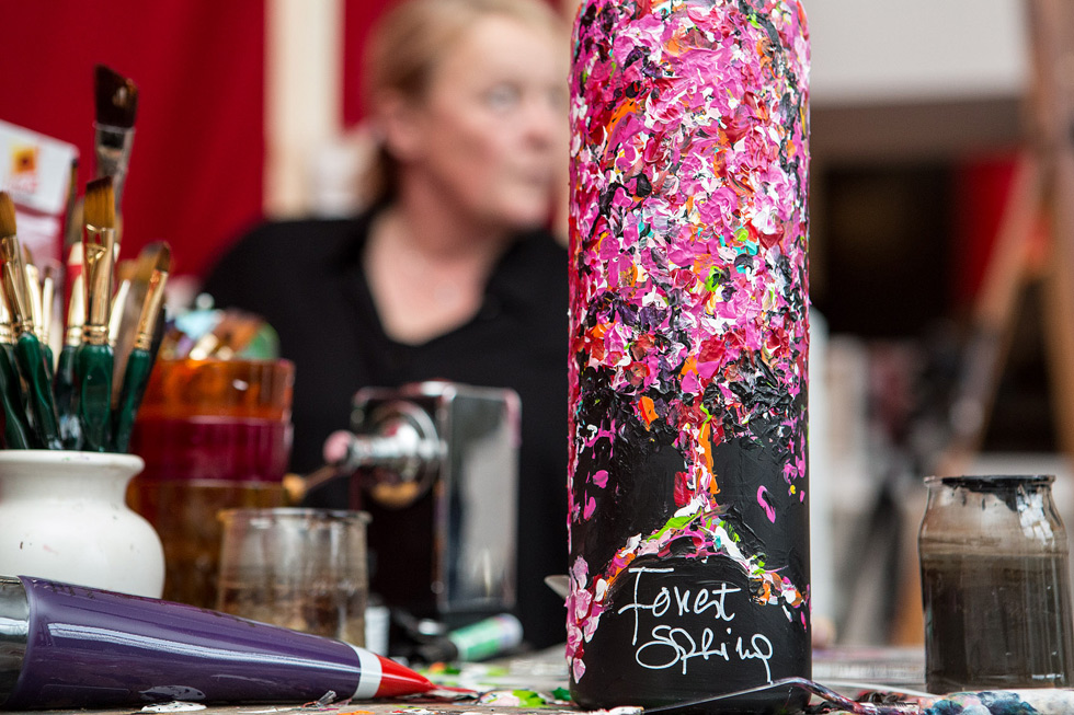 One of the bottles painted by Liesbeth Swinnen with the artist herself on the background