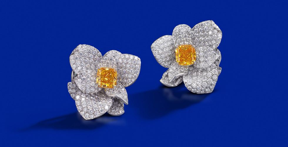 A rare pair of fancy coloured diamond and diamond earrings.  Each floral earring centring a radiant-cut fancy vivid yellowish orange diamond weighing 2.87 carats, and a radiant-cut fancy vivid yellow-orange diamond weighing 2.53 carats. Est. $ 360,00 – $ 490,000