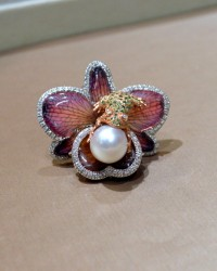 Cocktail ring with a rose gold frog sitting on a dried orchid covered in resin and holding a fresh water pearl by Francs V