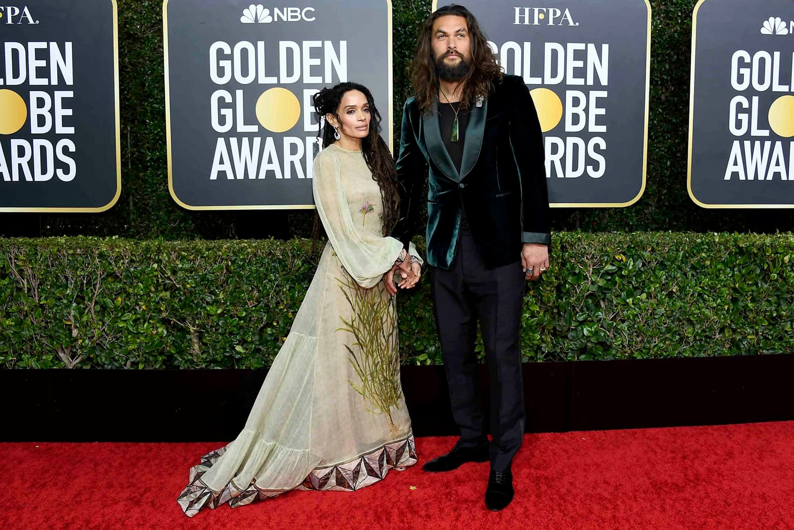 Lisa Bonet wearing Fernando Jorge chalcedony and diamond earrings, and her husband Jason Momoa wearing a Cartier Art Deco style brooch with onyx, emerald and diamonds in white gold, and 46mm Ballon Bleu de Cartier watch in rose gold, as well as his own jade pendant and rings
