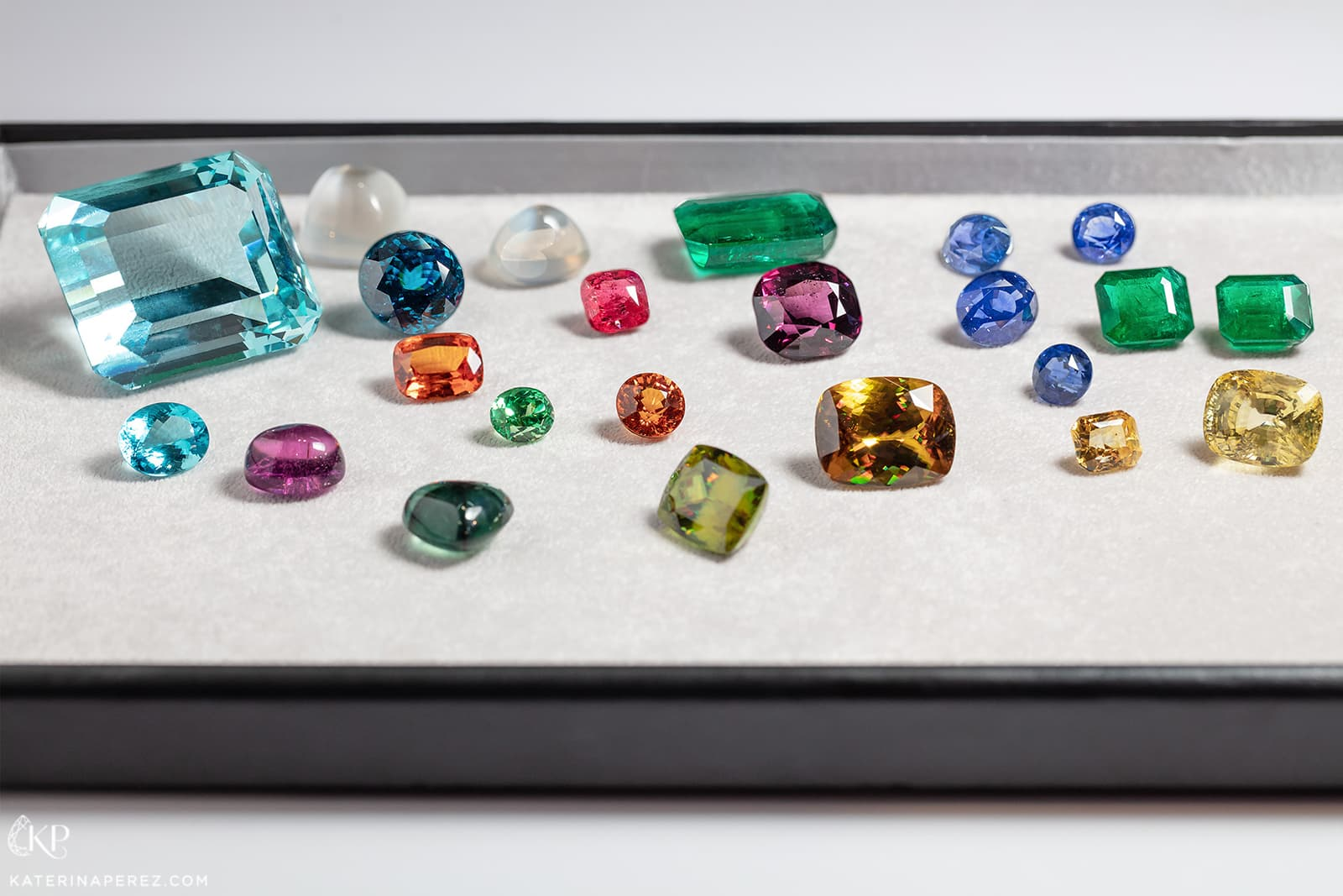 P&P Gems selection of gemstones including 450 cts Brazilian aquamarine, Paraiba tourmalines, emeralds, sphenes, spessartite garnets, moonstone and spinels. Photo by Simon Martner