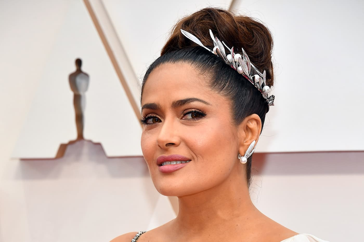 Salma Hayek wearing Boucheron Feuilles de Laurier necklace as headpiece and earrings, both with diamonds and pearls in white gold