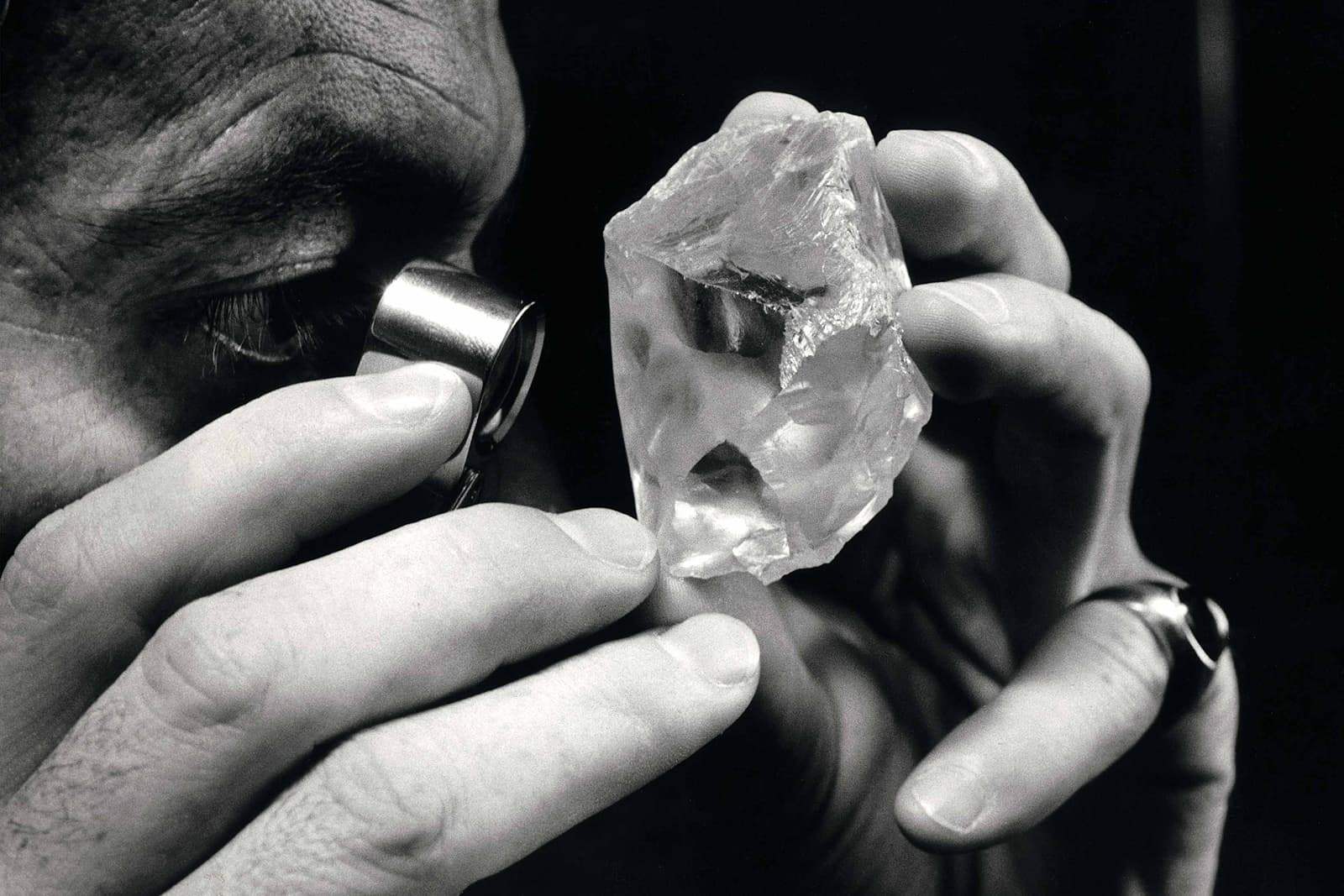 A gemmologist uses a loupe to examine the 603-carat Lesotho Promise rough diamond