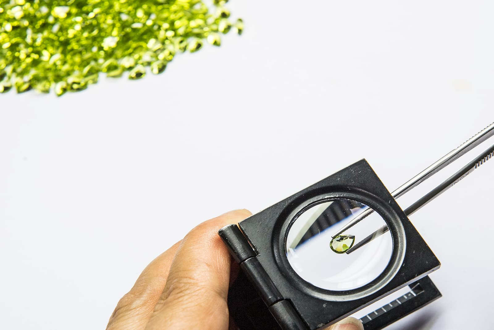 A faceted Fuli Gemstones peridot is examined beneath a magnifying glass
