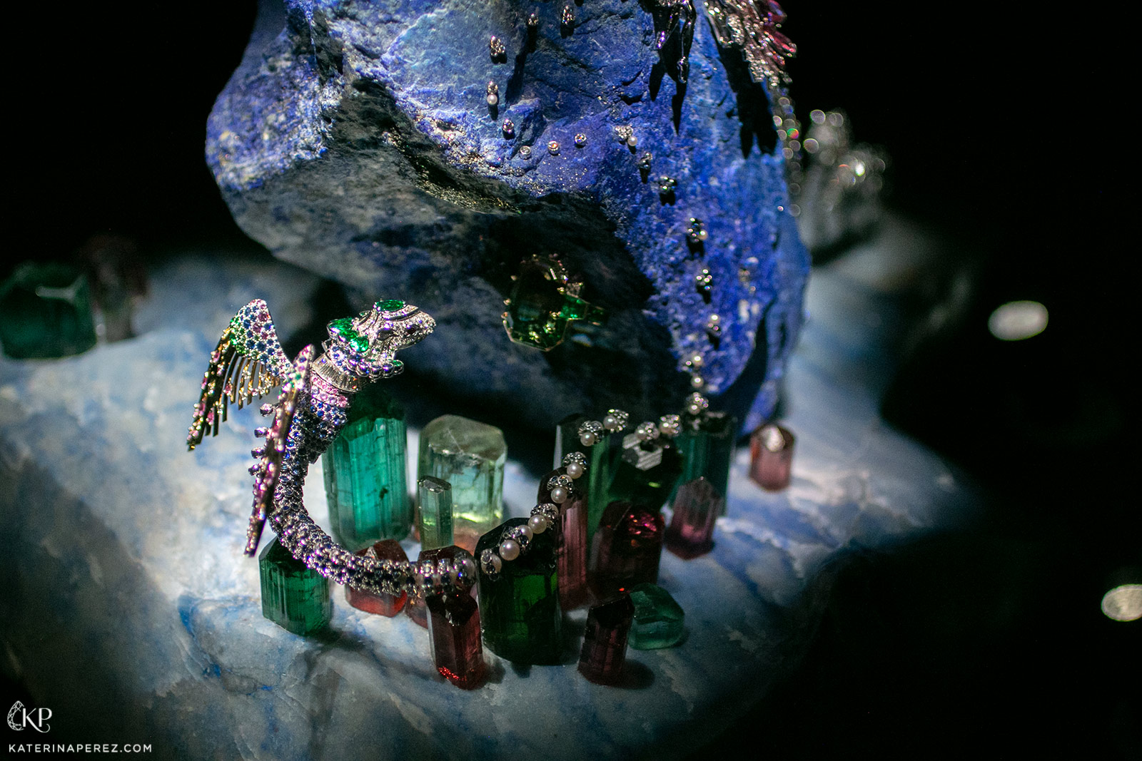 Perched on crystals of tourmaline, a gem-set chimera spreads its precious wings