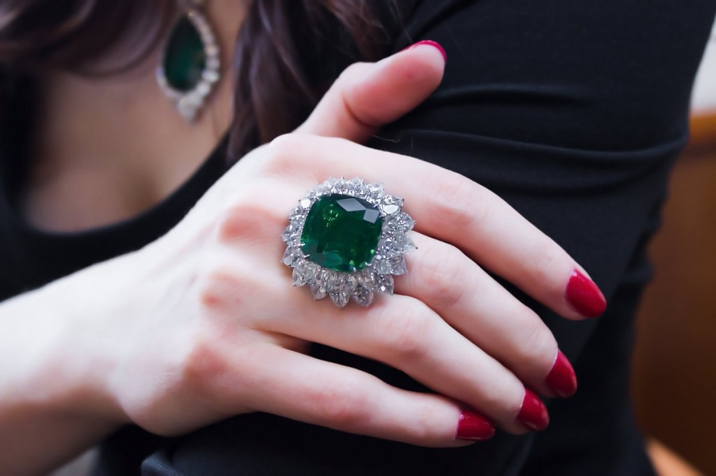 A ring centered upon a gem quality 22cts cushion-cut Colombian emerald set within a double row of pear-shaped diamonds