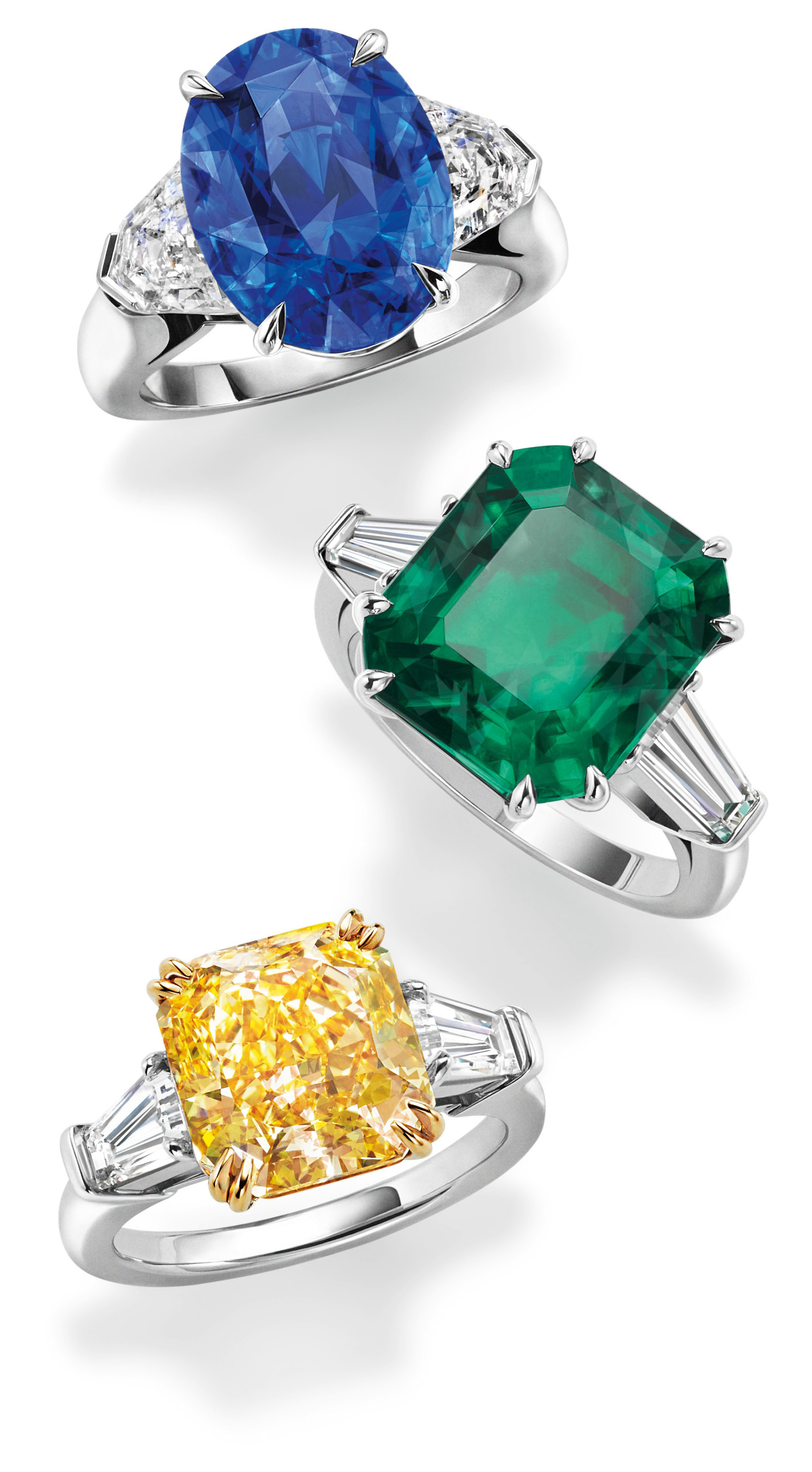 Harry Winston rings with an oval sapphire, an emerald cut emerald and a cushion cut yellow diamond