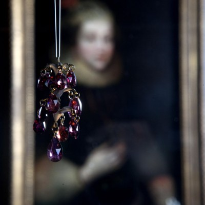 A garnet pendant hanging in front of a portrait of Elizabeth Wriothesley, Countess of Southampton