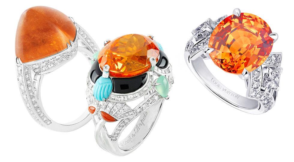 From left to right: Boucheron Joy ring with sugar loaf mandarin garnet and diamonds; Van Cleef&Arpels ring with diamonds, turquoise, coral, chrysoprase, onyx and 1 oval-cut Mandarin garnet of 15.77 carats; Louis Vuitton Acte V Genesis ring with an oval mandarin garnet and diamonds