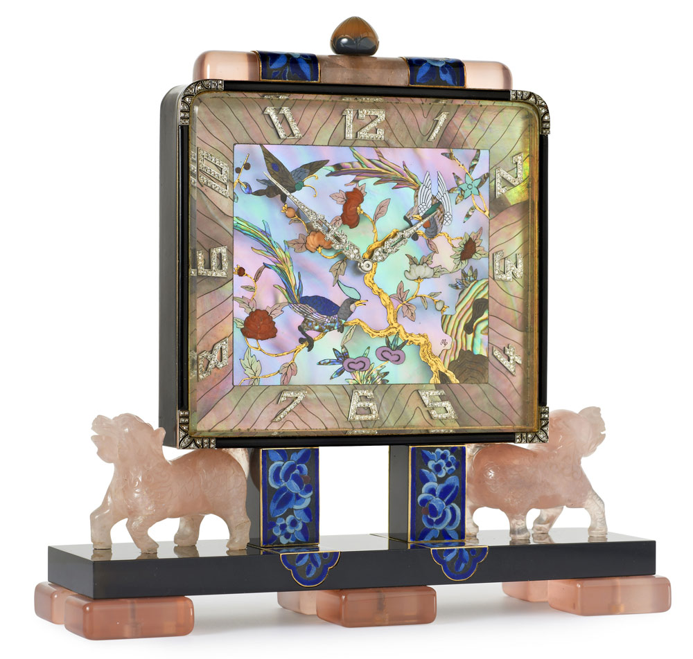 Exquisite Art Deco Chinoiserie desk clock with a rectangular dial of mother-of-pearl with floral and bird decoration enhanced by carved coral, applied rose-cut diamond Arabic chapters and pavé-set diamond hands. Black laquer case with rose quartz surmount, a carved agate crown and blue enamel floral panels, all on carved rose quartz dogs and blue enamel floral pillars. The black laquer base has six rose quartz feet and case contains a mechanical movement. By Lacloche Freres, Paris c1925 with dial decoration by Vladimir Makovsky
