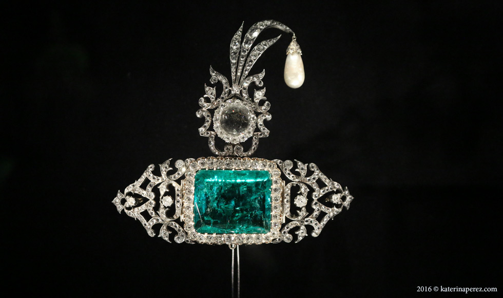 Turban ornament set in silver, the central emerald and diamonds set in gold. India, c.1900. The platinum pin with a feather was added by Cartier in 2012